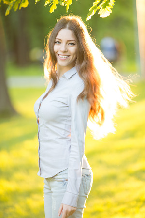 nature beauty: Romantic young girl outdoors enjoying nature Beautiful Model in Casual jeans in sun light Long healthy Hair Blowing in the Wind Backlit Warm Color Tones Beauty Sunshine woman Smiling Sunny Summer Day Autumn Summertime Glow Sun