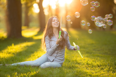 love park: Young spring fashion casual woman blow bubbles in the sunset in park Springtime Summertime Trendy girl sitting on  grass in  sunset Spring summer landscape background.  Sun rays. Summer scene Sunlight background.  Backlit.