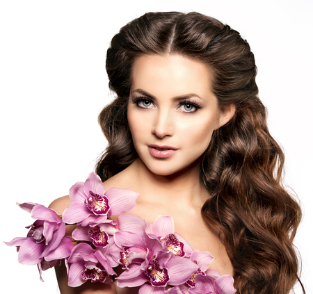 hair model: Beauty young woman, luxury long curly hair with orchid flower. Haircut. Beautiful girls fresh healthy skin, makeup, lips, eyelashes. Fashion model in spa care salon. Sexy trendy hairstyle look. Stock Photo