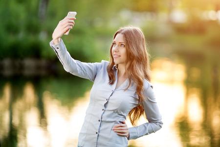iluminado a contraluz: Chica joven romántica celebración de una cámara digital, teléfono inteligente con las manos y tomar un retrato selfie auto de sí misma al aire libre disfrutando la naturaleza Hermosa mujer Urbano Modelo en pantalones vaqueros ocasionales de sol ligh retroiluminados tonos cálidos de color