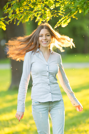 young beautiful woman: Romantic young girl outdoors enjoying nature Beautiful Model in Casual jeans in sun light Long healthy Hair Blowing in the Wind Backlit Warm Color Tones Beauty Sunshine woman Smiling Sunny Summer Day Autumn Summertime Glow Sun