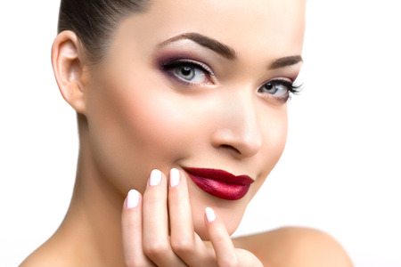 maquillaje de ojos: Mujer modelo hermosa en la belleza del maquillaje del salón Joven moderna en el spa de lujo Señora componen rimel para pestañas largas lápiz labial en los labios ojo sombra manicura pelo brillante con el clavo Productos esmalte Tratamiento