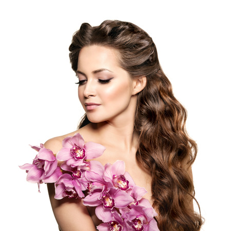 sexy young girls: Beauty young woman, luxury long curly hair with orchid flower. Haircut. Beautiful girls fresh healthy skin, makeup, lips, eyelashes. Fashion model in spa care salon. Sexy trendy hairstyle look. Stock Photo