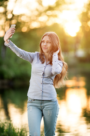 ligh: Romantic young girl holding a smartphone digital camera with her hands and taking a selfie self portrait of herself outdoors enjoying nature Beautiful Urban Model woman in Casual jeans in sun ligh  Backlit Warm Color Tones