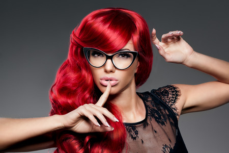 Luxury fashion trendy  young  woman with red curled hair in glasses. Optics. Girl with beauty hairstyle. Model with long stylish  bangs, wave, curly hair. Lady with a beauty face. Secret, gossip, news Stock Photo
