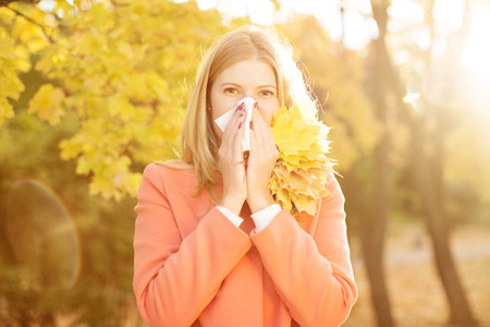 Girl with cold rhinitis on autumn background. Fall flu season.