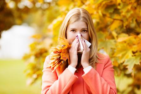 chory: Dziewczyna z zimną nieżytu nosa na tle jesieni.