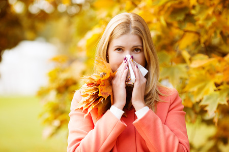 Girl with cold rhinitis on autumn background.  Banco de Imagens