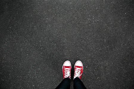 Gumshoes su sfondo urbano grunge di asfalto. Immagine concettuale di gambe in stivali sulla strada cittadina. piedi scarpe che camminano in outdoor. Gioventù Selphie pantaloni a vita bassa moderna