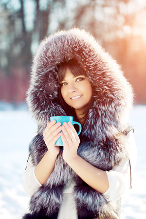 girl in a hat: Young woman with a cup of hot drink in winter wood
