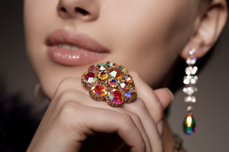 jewelry: Diamond. Brilliant. Antique old vintage earrings and ring. Jewelry on her finger at the girl close-up on a