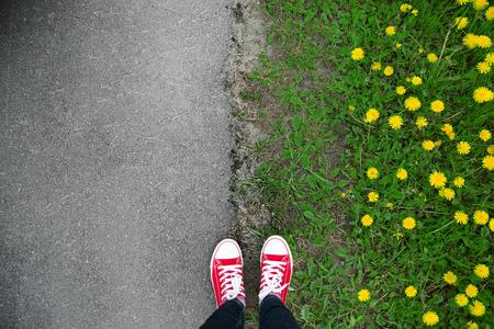 pieds sales: Gumshoes sur urbain grunge fond d'asphalte. Image conceptuelle de jambes en bottes sur rue de la ville. chaussures de pieds marchant dans extérieur. Selphie jeunesse hippie moderne