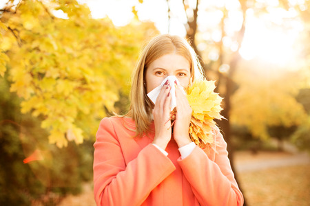 rheum: Girl with cold rhinitis on autumn background.  Stock Photo