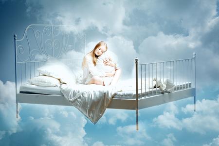 deitado: Mulher de sono. Menina com um travesseiro e cobertor sobre a cama entre as nuvens em sonhos