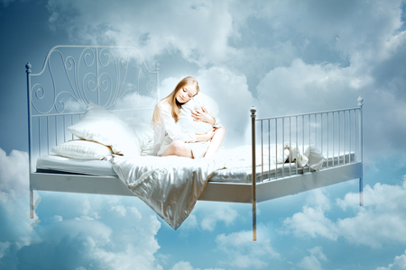 sleeping girl: Sleeping woman. Girl with a pillow and blanket on the bed among the clouds in dreams