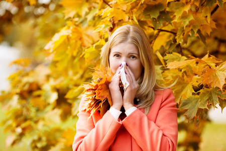 Girl with cold rhinitis on autumn background.  Standard-Bild