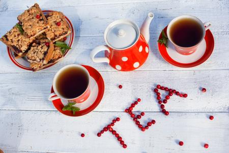 taza de té: Tazas de té Vista superior. La hora del té para la fiesta. Conjunto de té de lunares rojos, galletas sobre un fondo de madera.