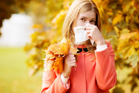 running nose: Girl with cold rhinitis on autumn background.  Stock Photo