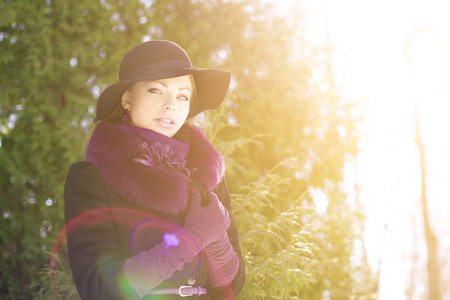 apparel: Winter woman on background of winter landscape, sun.