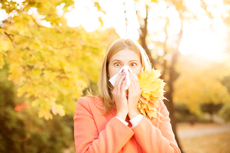 Girl with cold rhinitis on autumn background.