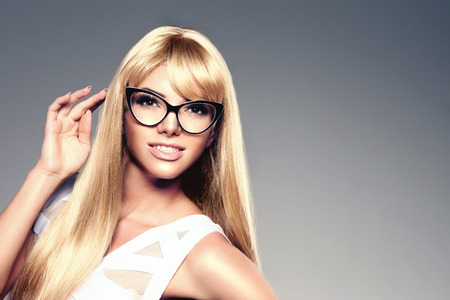 sexy young girls: Beauty young woman, luxury long blond hair in glasses. Haircut, fringe. Girls fresh healthy skin, makeup, lips, eyelashes, manicured nails shiny. Fashion model in spa care salon. Sexy trendy hairstyle look.