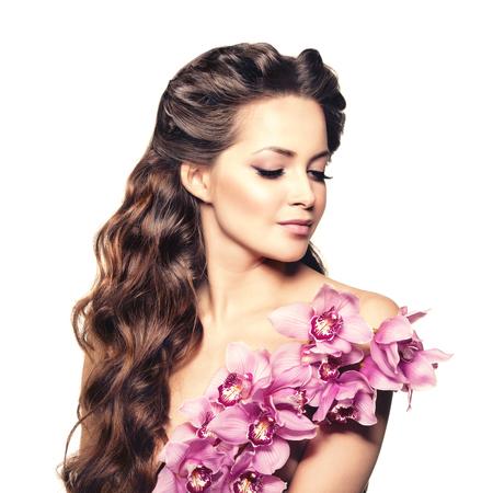 labios sexy: Joven mujer de la belleza, pelo largo y rizado de lujo con flor de la orquídea. Corte de pelo. Las muchachas hermosas frescas sanas de la piel, maquillaje, labios, pestañas. Modelo de moda en el salón de cuidado de hidromasaje. Mirada atractiva peinado de moda. Foto de archivo