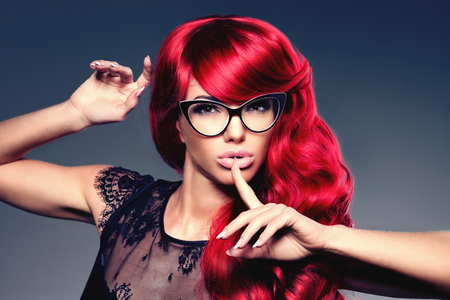 woman hairstyle: Luxury fashion trendy  young  woman with red curled hair in glasses. Optics. Girl with beauty hairstyle. Model with long stylish  bangs, wave, curly hair. Lady with a beauty face. Secret, gossip, news Stock Photo
