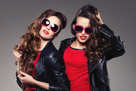 glamour shopping: Sisters twins in hipster sun glasses laughing Two fashion models Women smiling positive Friends group having fun, talking Youthful friendship youth adults people culture concept Young girls rock party Stock Photo