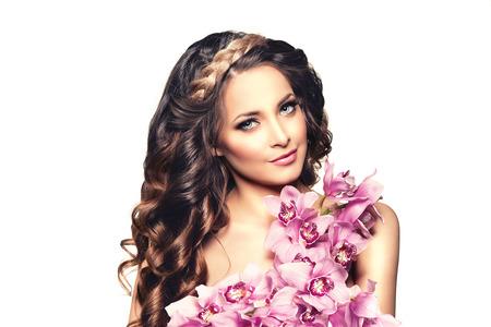 sexy young girls: Молодая женщина красота, роскошь длинные вьющиеся волосы с цветок орхидеи. Стрижка. Красивые девушки свежие здоровой кожи, макияж, губы, ресницы. Мода модель в салоне спа ухода. Сексуальная модные прически взгляд.