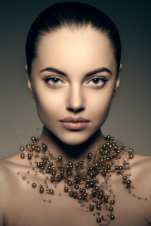 High-fashion Model Girl. Beauty Woman high fashion Vogue Style Portrait of beautiful fashionable girl Luxury lady with precious jewelery of pearls around her neck, necklace  Stylish Makeup,  Make up Perfect skin, eyes and lips