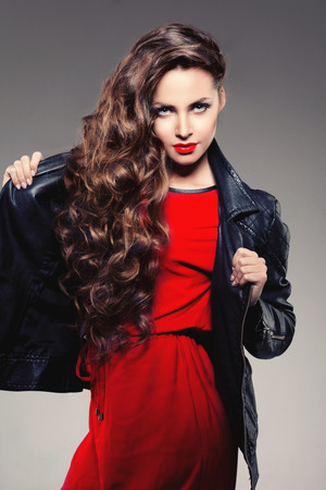 hairstyle health: Beautiful young woman model brunette with long curled hair with red lips in leather jacket. Girl wave, curly hairstyle. Health hair shine. Beauty lady face with sexy glance.