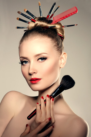 Beauty young girl model stylist with brushes in volume hairstyle. Woman with bright luxurious makeup, long eyelashes with mascara, neat manicure, red lipstick
