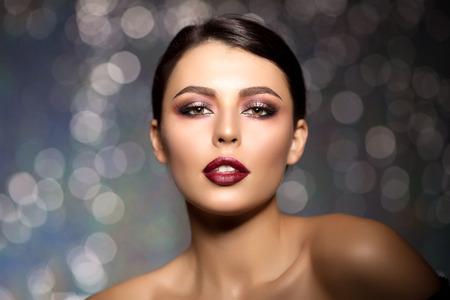 lipstick: Mujer modelo hermosa en la belleza del maquillaje del salón Joven moderna en el spa de lujo Señora componen rimel para pestañas largas lápiz labial en los labios ojo sombra manicura pelo brillante con el clavo Productos esmalte Tratamiento