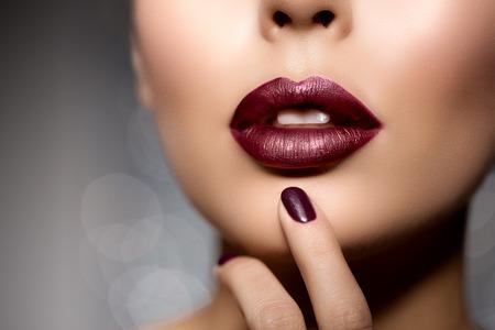 beso labios: labios rojos de la mujer de cerca. modelo muchacha hermosa con lápiz de labios, manicura con esmalte de uñas para tratamientos