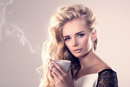 greem: Model with coffee cup, mug in coffee shop. Fashion Woman, tea party time. Greem Black. Blonde girl, tea set