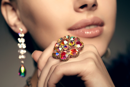 expensive: Diamond. Brilliant. Antique old vintage earrings and ring. Jewelry on her finger at the girl close-up on a