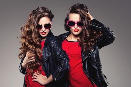 amicizia: Sorelle gemelli in vita bassa occhiali da sole a ridere Due modelli di moda le donne sorridenti gruppo positivo Amici divertirsi, parlare giovanile amicizia giovani adulti persone coltura concetto Giovani ragazze roccia partito