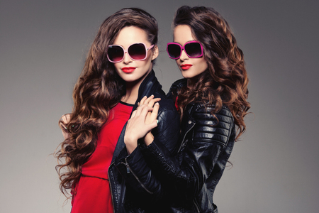youth group: Sisters twins in hipster sun glasses laughing Two fashion models Women smiling positive Friends group having fun, talking Youthful friendship youth adults people culture concept Young girls rock party Stock Photo