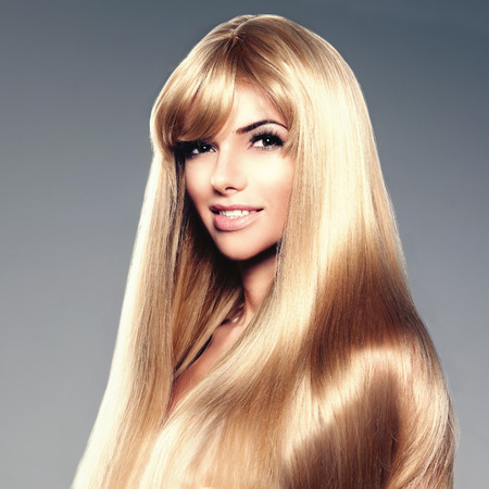 Beauty young woman with luxurious long blond hair. Haircut with fringe. Girl with fresh healthy skin, prifessional makeup, red lips, long eyelashes and manicured nails shiny. Fashion model in spa hair care salon. Girly trendy hairstyle look.