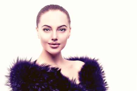 outerwear: Woman in a fur coat. Young beautiful model in winter outerwear. Stylish luxury girl on a white background Stock Photo