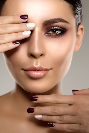 l�piz labial: Mujer modelo hermosa en la belleza del maquillaje del sal�n Joven moderna en el spa de lujo Se�ora componen rimel para pesta�as largas l�piz labial en los labios ojo sombra manicura pelo brillante con el clavo Productos esmalte Tratamiento