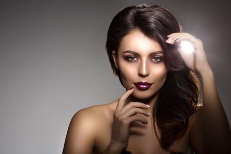 Belle femme de modèle dans un salon de beauté maquillage Jeune fille moderne spa luxueux Lady maquillage Mascara pour les longs cils de rouge à lèvres sur les lèvres fard à paupières brillant manucure cheveux avec du vernis à ongles Produits de traitement