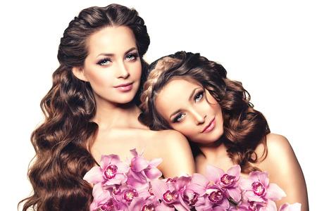 sexy young girls: Две молодые женщины красоты, роскоши длинные вьющиеся волосы с цветок орхидеи. Стрижка. Красивые девушки свежие здоровой кожи, макияж, губы, ресницы. Мода модели в салоне спа ухода. Сексуальная модные прически взгляд.