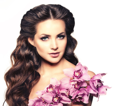 attractive gorgeous: Beauty young woman, luxury long curly hair with orchid flower. Haircut. Beautiful girls fresh healthy skin, makeup, lips, eyelashes. Fashion model in spa care salon. Sexy trendy hairstyle look. Stock Photo