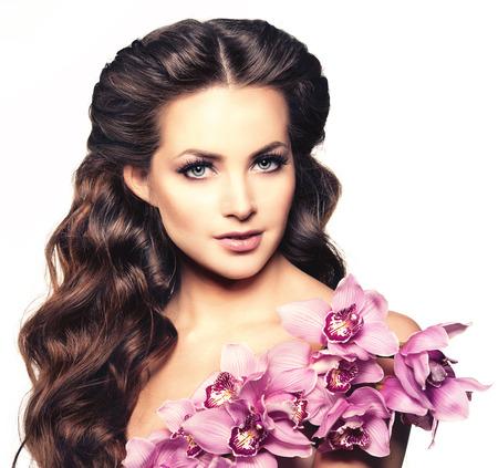 cabello rizado: Joven mujer de la belleza, pelo largo y rizado de lujo con flor de la orquídea. Corte de pelo. Las muchachas hermosas frescas sanas de la piel, maquillaje, labios, pestañas. Modelo de moda en el salón de cuidado de hidromasaje. Mirada atractiva peinado de moda. Foto de archivo