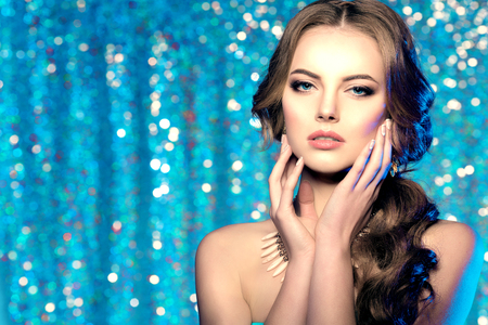 Winter woman model gorgeous beauty makeup stylish hairstyle. Young girl on the background bokeh. Lady make up Mascara for long lashes lipstick on lips eye shadow shiny hair manicure with nail polish Products Treatment Standard-Bild