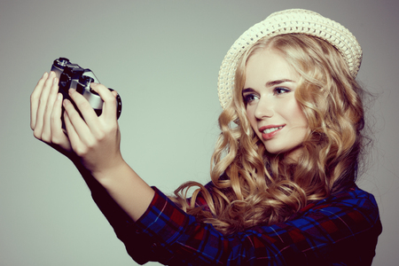 color hair: Young woman with camera. Blonde in a plaid shirt. Hipster fashion photographer girl. Young people, youth culture