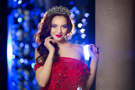 Woman in lux dress with crown like queen, princess, lights party background Luxury girl Long shiny healthy volume hair. Waves Curls Updo Hairstyle. Salon Fashion model, luxurious haircut, vintage interior. Jewelry Earrings