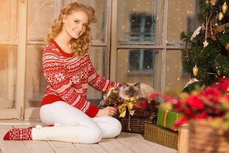 fiesta de navidad, vacaciones de invierno Mujer con el gato. niña de año nuevo. el árbol de navidad en el fondo interior.