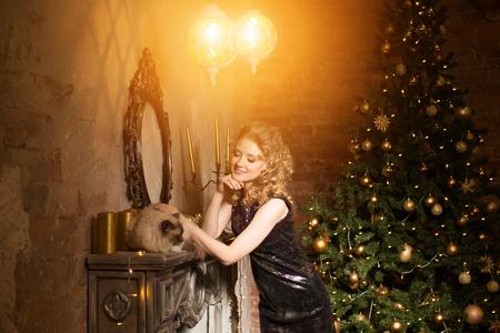 navidad elegante: fiesta de navidad, vacaciones de invierno Mujer con el gato. niña de año nuevo. el árbol de navidad en el fondo interior. Foto de archivo